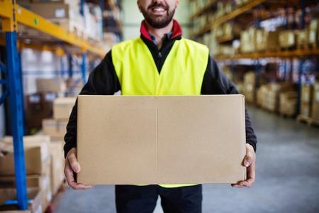 大きな箱を持つ男性倉庫作業員。