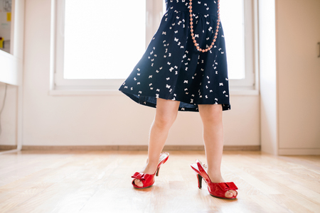 Unrecognizable little girl in dress and red high heels at home.