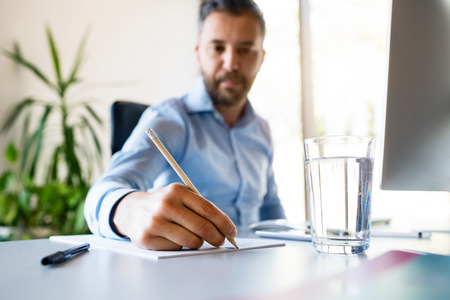 Young businessman in his office writing something with pencil. Stock Photo