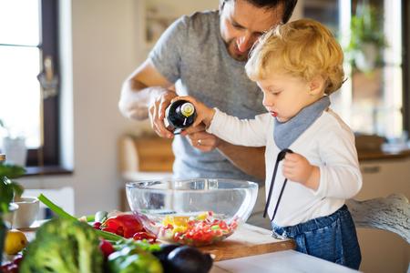Jonge vader met peuterjongen het koken.
