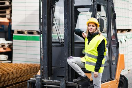 Vrouwenvorkheftruckchauffeur op een industriezone. Stockfoto