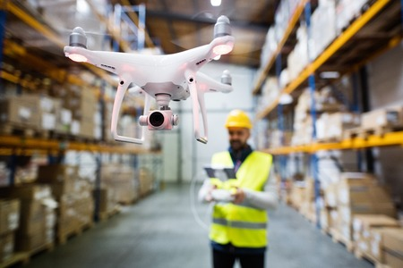 Man with drone in a warehouse. Archivio Fotografico