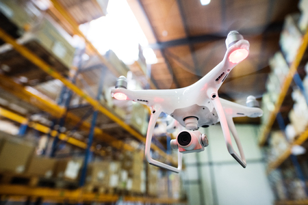 White drone flying inside the warehouse. Reklamní fotografie
