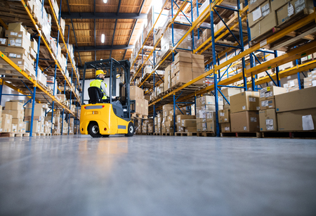 Warehouse man worker with forklift. Stock Photo