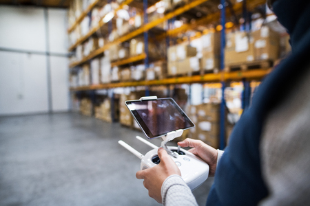 Man with tablet and drone controller in a warehouse. Banque d'images