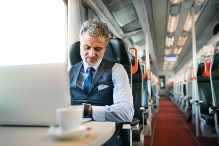 Mature businessman with laptop travelling by train. Stock fotó - 91912142