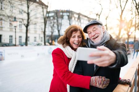Ältere Paare mit Smartphone auf einem Spaziergang in einem Stadt im Winter Standard-Bild