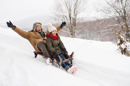 Grootvader en klein meisje sleeën op een winterdag.