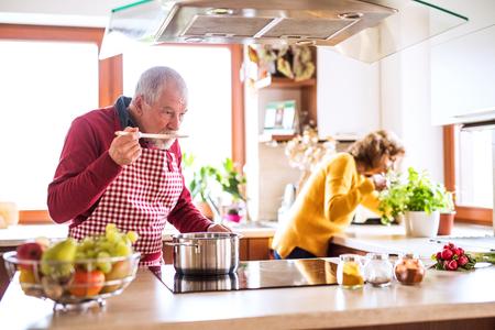 Coppie senior che preparano alimento nella cucina.