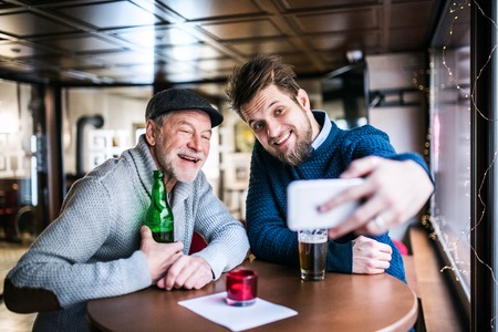 Senior father and his young son drinking beer in a pub. A young man taking selfie with smartphone.