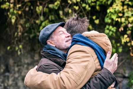 Lterer Vater und sein kleiner Sohn auf einem Spaziergang, umarmend. Standard-Bild - 92049918