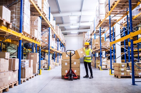 Female warehouse worker loading or unloading boxes.
