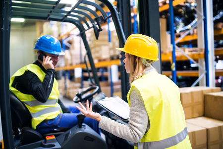 Young warehouse workers working together. Man with a smartphone, making a phone call and woman holding notes, checking something. Stock Photo