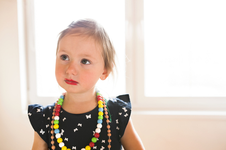 Cute little girl in dress at home wearing red lipstick. Banque d'images