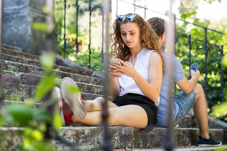 Young couple with smartphones sitting on stairs in town. Banque d'images