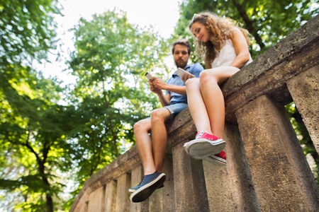 Young couple with smartphones in town sitting on concrete wall. Banque d'images