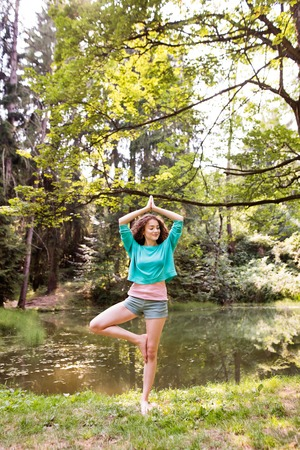 Beautiful girl practices yoga in the morning forest. Banque d'images