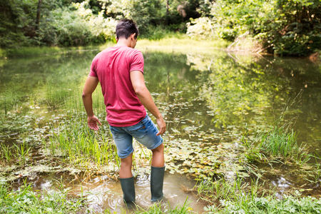 Teenage boy in rubber boots standing in lake.