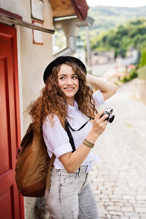 Beautiful young tourist with camera in the old town. Banque d'images