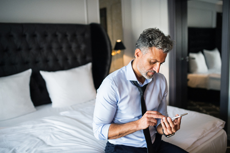 Mature businessman with smartphone in a hotel room. Stock Photo - 93718640