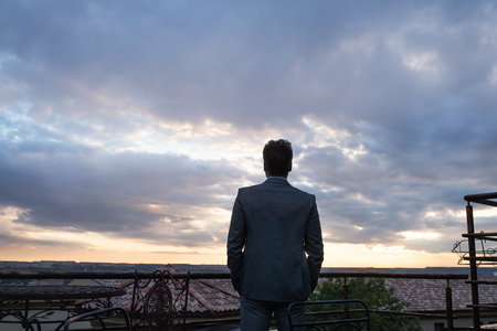 Mature businessman standing in a hotel balcony in the evening. Rear view.