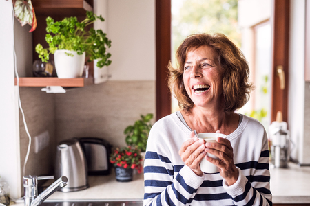 台所でコーヒーを飲んでいる先輩女性。 写真素材