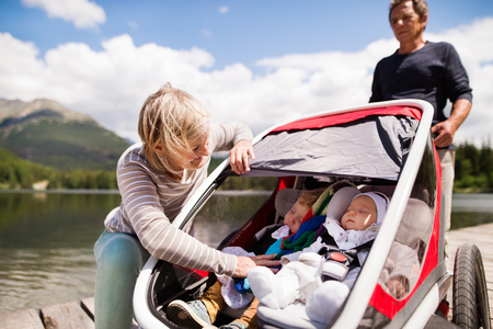 Senior couple with grandchildren in jogging stroller. Stock Photo