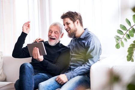 Hijo del inconformista y su padre mayor con la tableta en casa. Foto de archivo