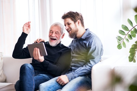 Hipster son and his senior father with tablet at home. Banco de Imagens