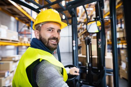 フォークリフトを持つ倉庫の男性労働者。