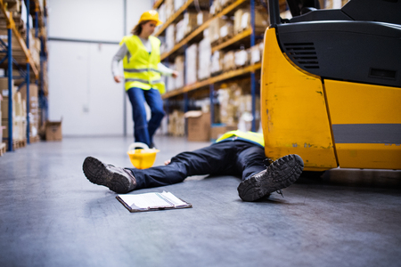 An injured worker after an accident in a warehouse. Stockfoto