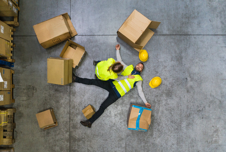Warehouse worker after an accident in a warehouse. Foto de archivo