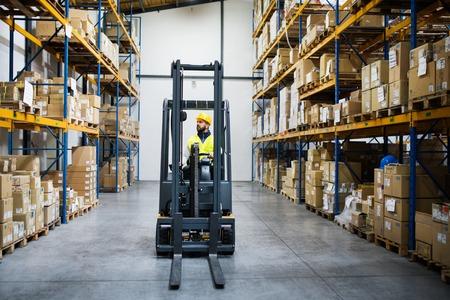 Warehouse man worker with forklift. Standard-Bild