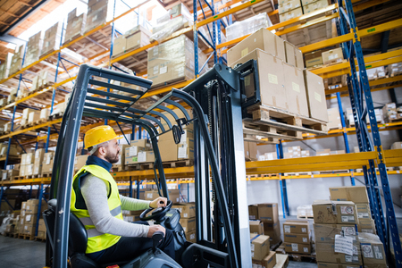 Warehouse man worker with forklift. 스톡 콘텐츠