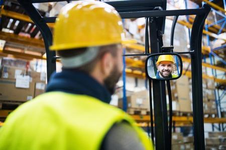 Warehouse man worker with forklift. Banco de Imagens