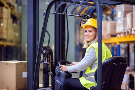 Woman warehouse worker with forklift. Foto de archivo