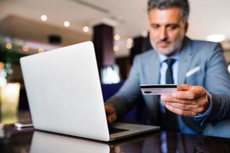 성숙한 사업가 호텔 라운지에서 노트북입니다.