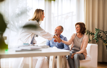 Female doctor talking to a senior couple.