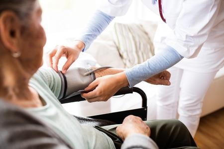 Nicht wiedererkennbarer Gesundheitsbesucher und eine ältere Frau während des Hausbesuchs. Eine Krankenschwester, die Blutdruck einer Frau in einem Rollstuhl überprüft.