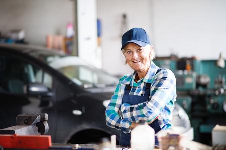 Senior female mechanic repairing a car in a garage. Reklamní fotografie - 94379838