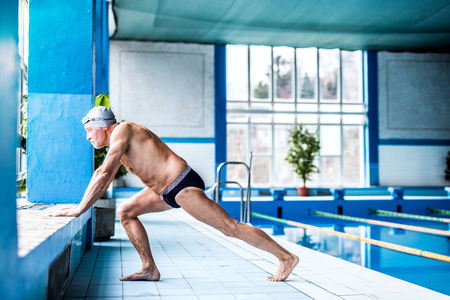 Senior man stretching by the indoor swimming pool.