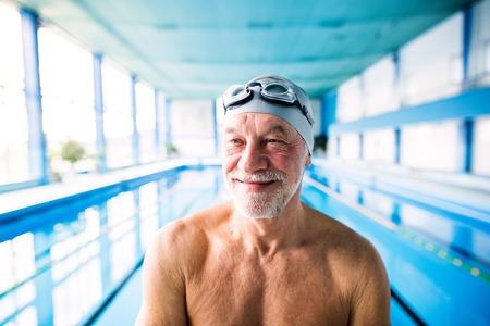 Senior man standing in an indoor swimming pool.