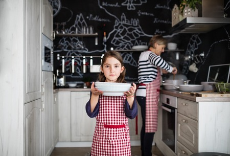 A small girl cooking with grandmother at home. Banco de Imagens