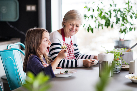 A small girl with grandmother at home. Stock Photo