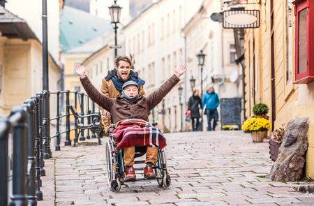 Senior vader in rolstoel en jonge zoon op een wandeling.