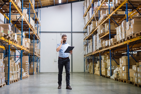 Warehouse worker or supervisor with a smartphone. Banco de Imagens