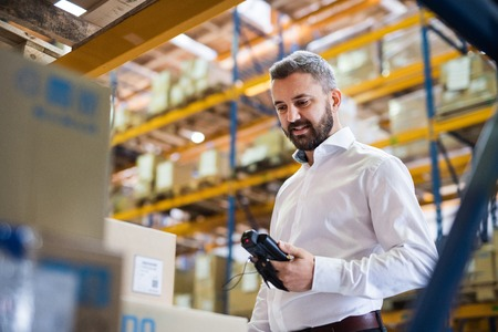 Warehouse worker or supervisor with barcode scanner. Stock Photo