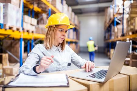 Jeunes ouvriers d'entrepôt avec ordinateur portable.