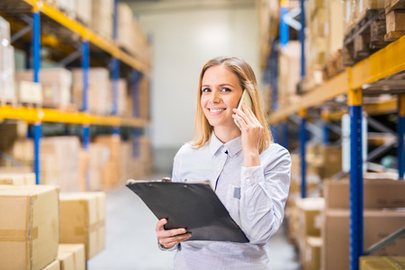 Woman warehouse worker or supervisor with smartphone. Banco de Imagens - 94574944