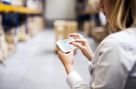女性倉庫労働者または上司をスマートフォンで使用。 写真素材